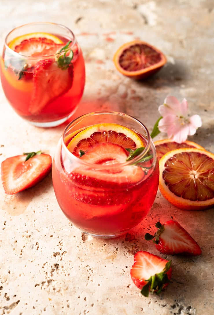 A campari cocktail in two round glasses garnished with fruit