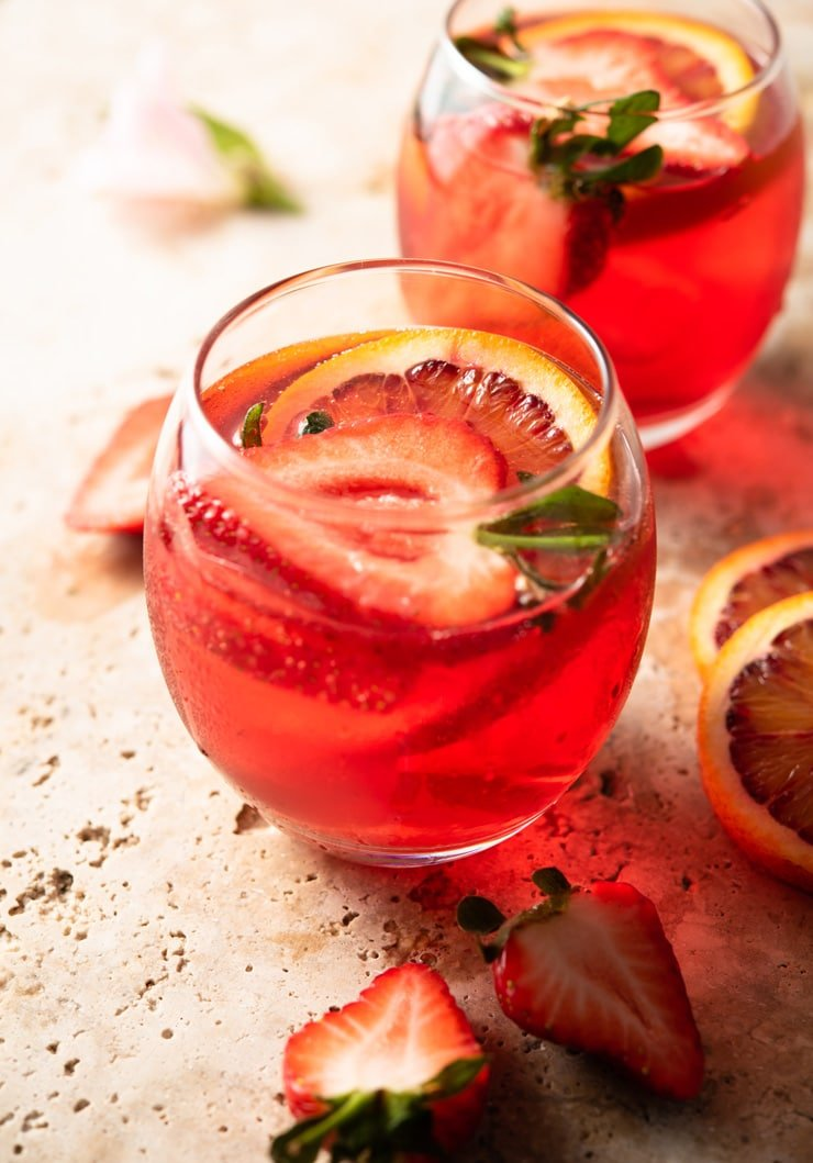 A close up of a campari spritz in a glass with fresh strawberries and oranges