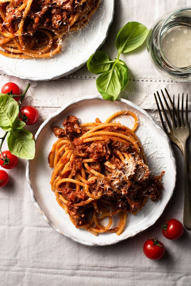 An overhead shot of leftover pulled pork ragu on a plate with wine and basil at the side