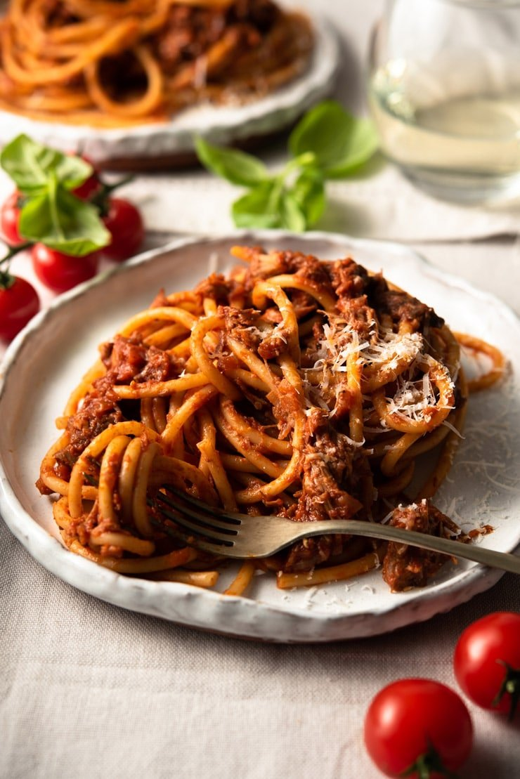 A close up of leftover pulled pork ragu with bucatini pasta on a plate
