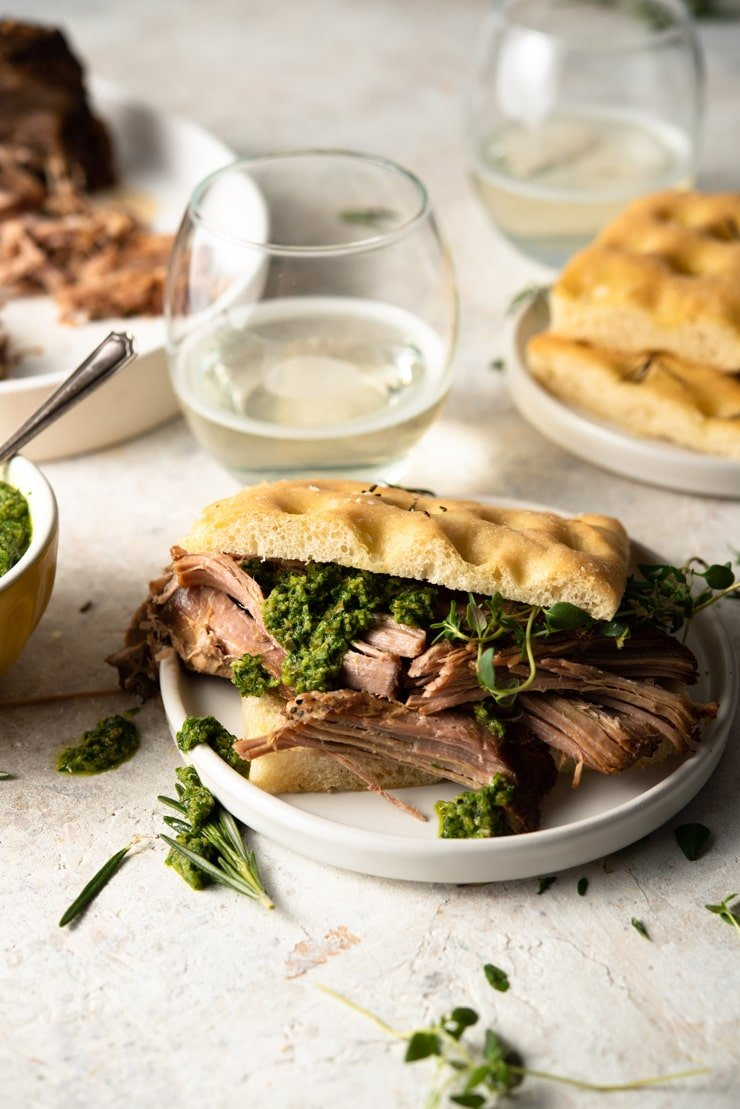 A focaccia sandwich with some slow cooker pulled pork shoulder and salsa verde