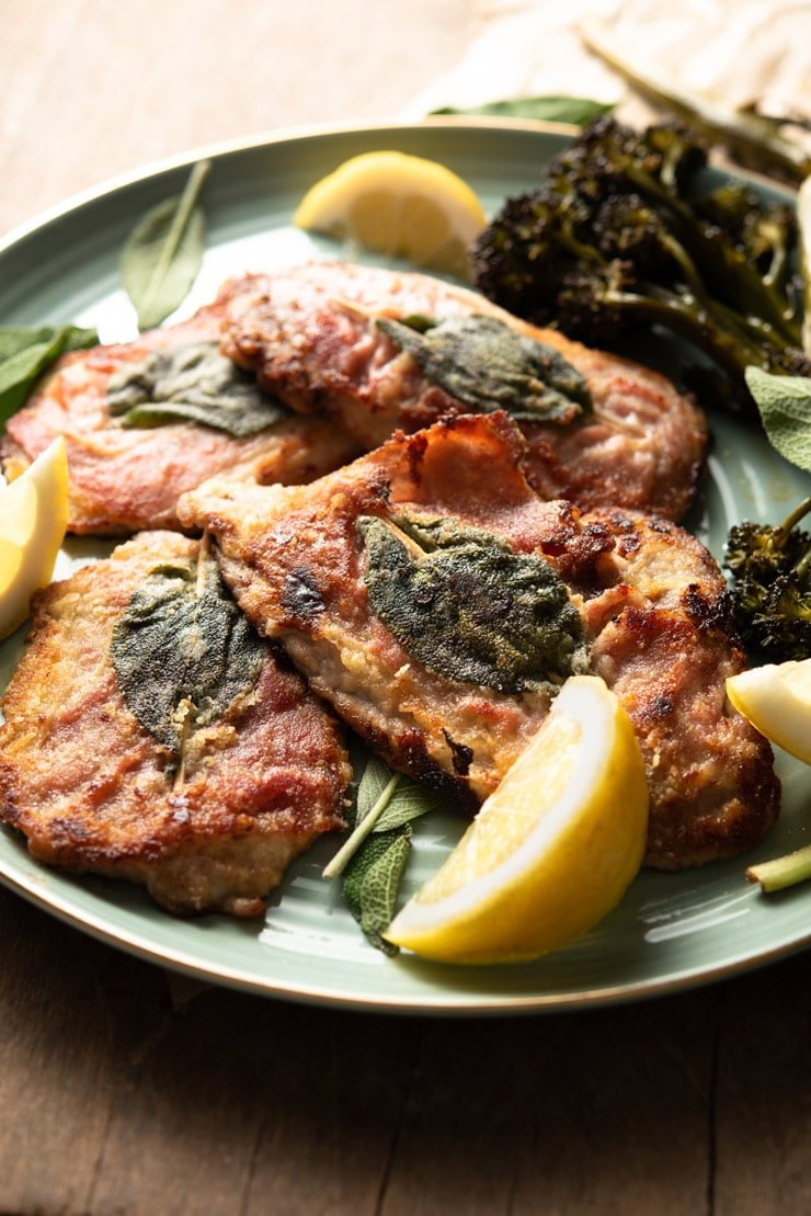 A side shot of veal saltimbocca with prosciutto and sage on a plate with lemon wedges