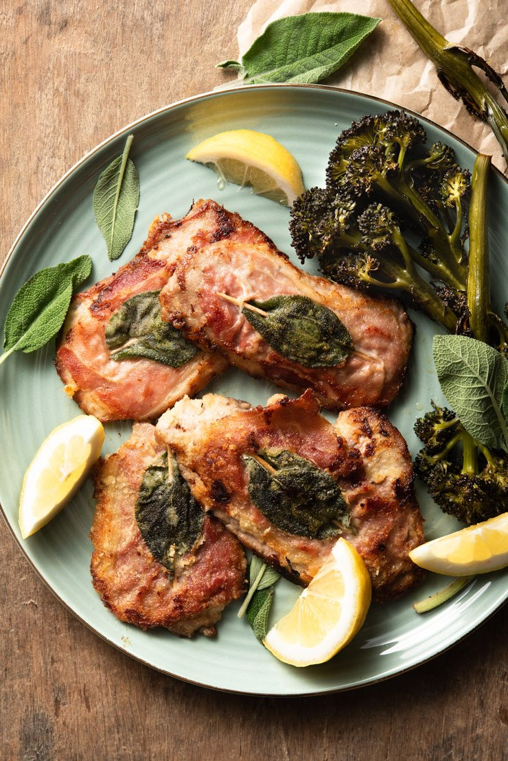 An overhead shot of veal saltimbocca on a plate with prosciutto, sage and lemon wedges