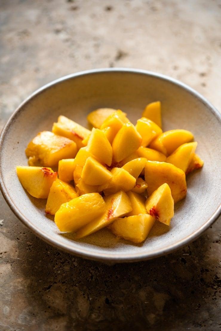 Chopped up fresh peaches in a bowl to make a peach bellini