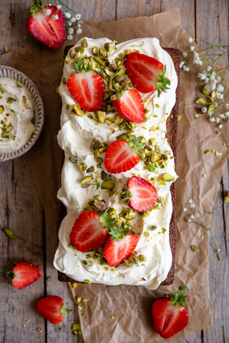 An overhead shot of a pistachio cake topped with whipped cream and fresh strawberries