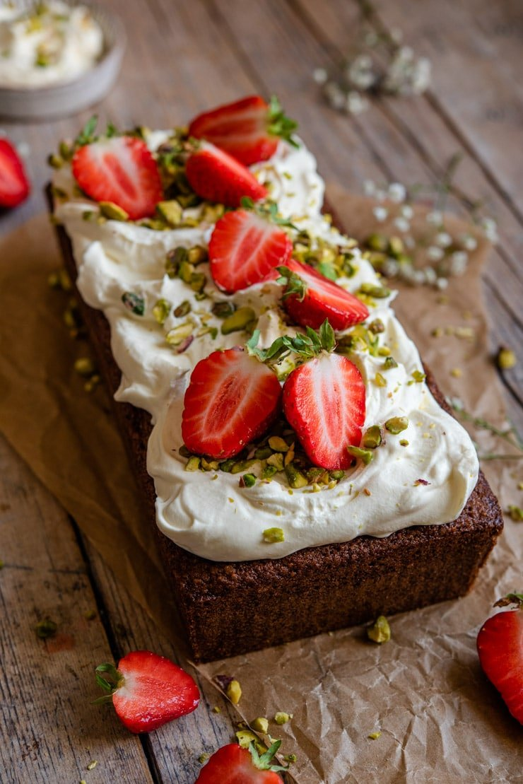 A side shot of a pistachio cake topped with whipped cream and strawberries
