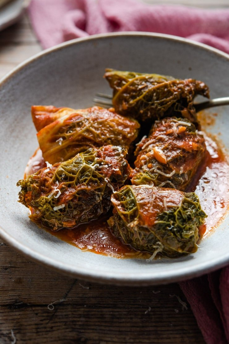 A close up of Italian stuffed cabbage rolls in a rustic bowl with tomato sauce