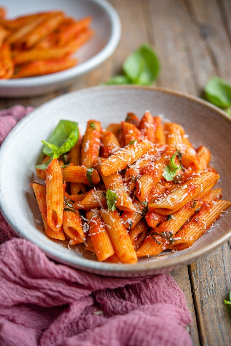 A side shot of penne pomodoro in a rustic bowl