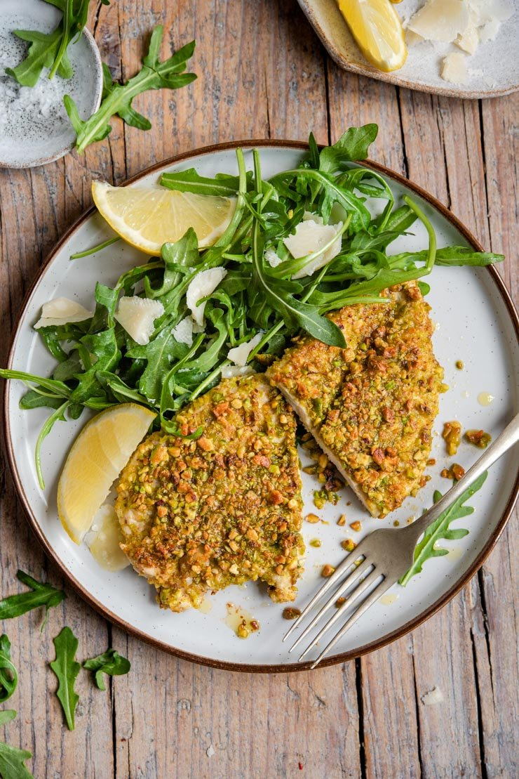 An overhead shot of pistachio crusted chicken on a plate with an arugula salad and lemon wedges