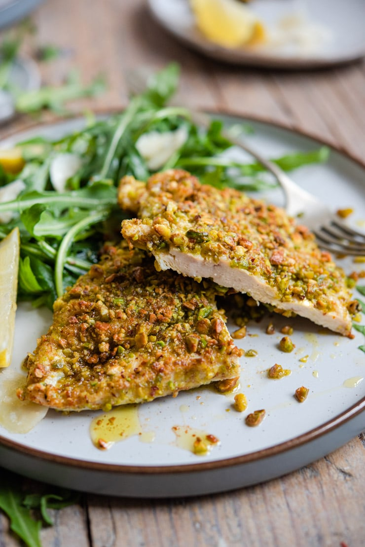 A close up of pistachio crusted chicken cut in half