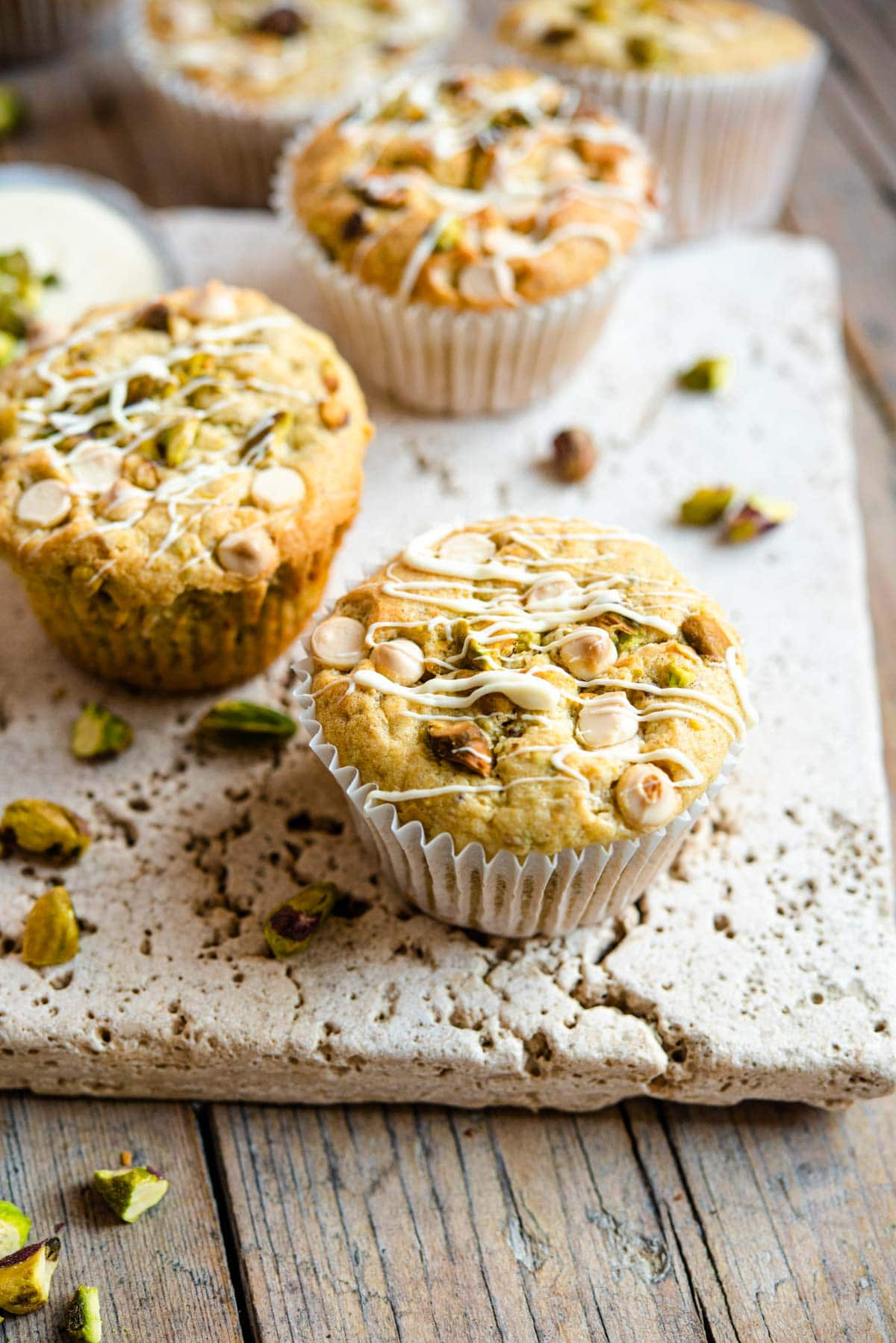A close up of a pistachio muffin topped with white chocolate chips