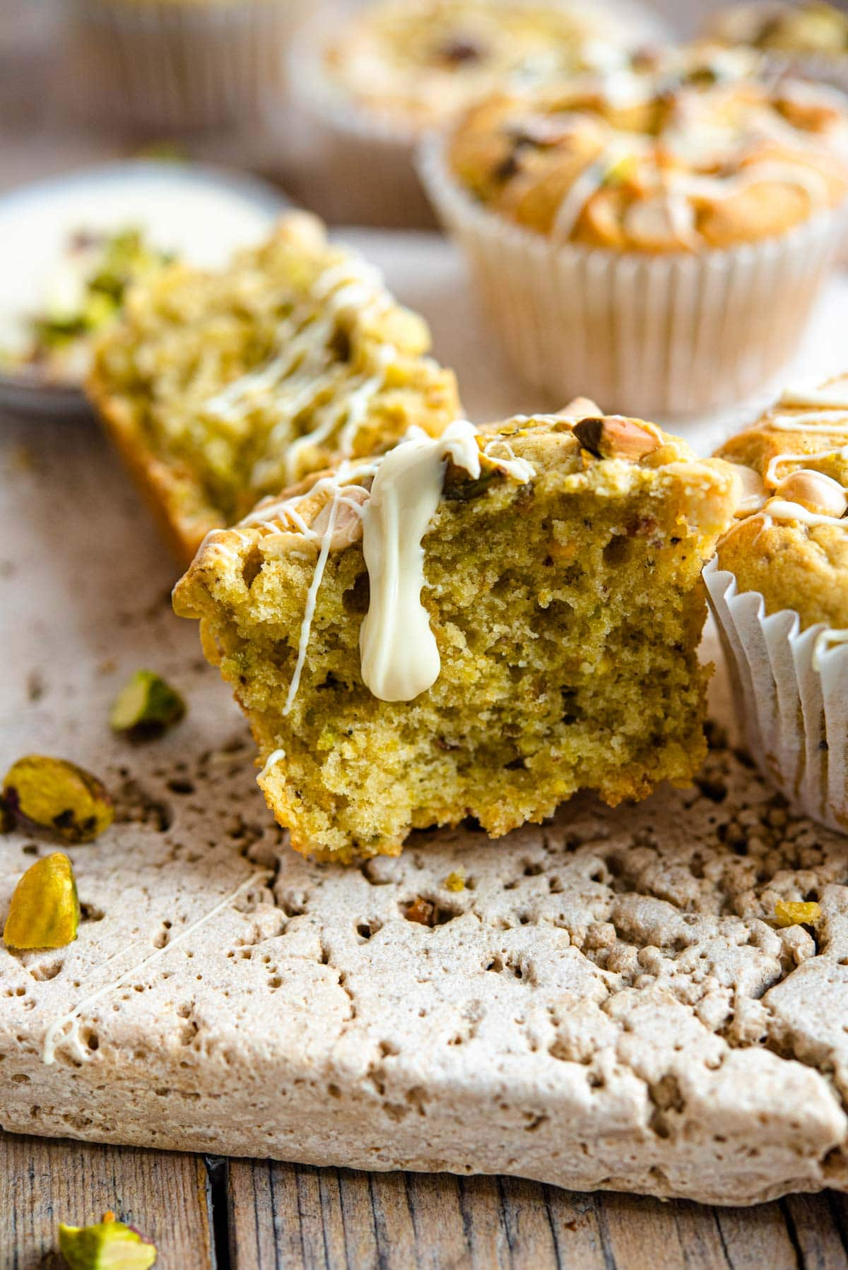 A close up of a pistachio muffin cut in half with white chocolate drizzled on top