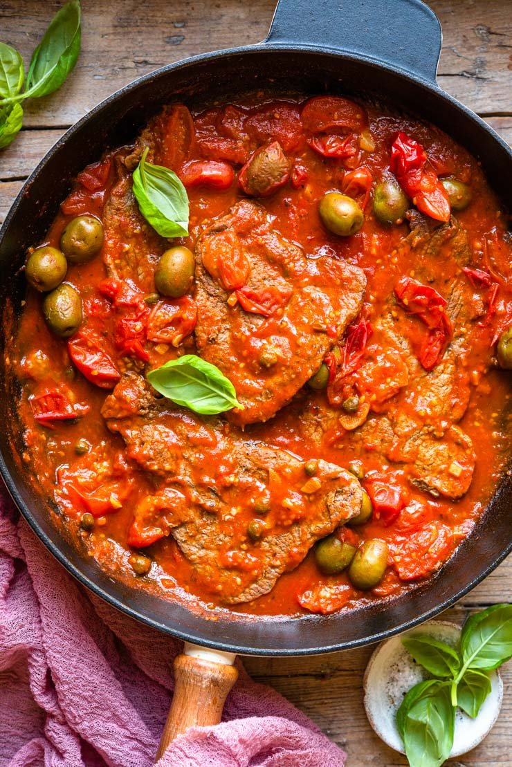 Overhead shot of a skillet with steak in a tomato sauce with olives and basil