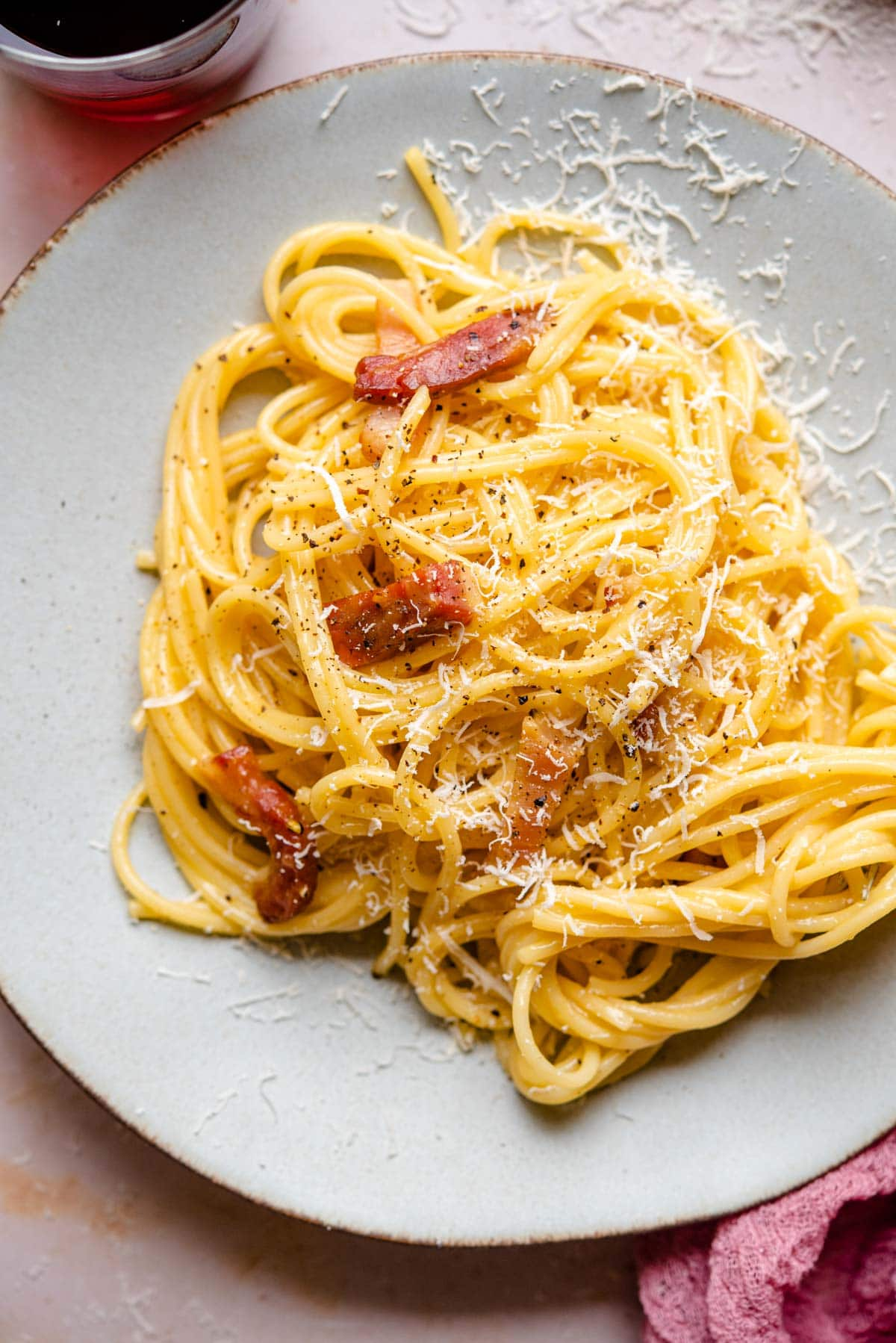 A close up of spaghetti on a plate with pieces of guanciale