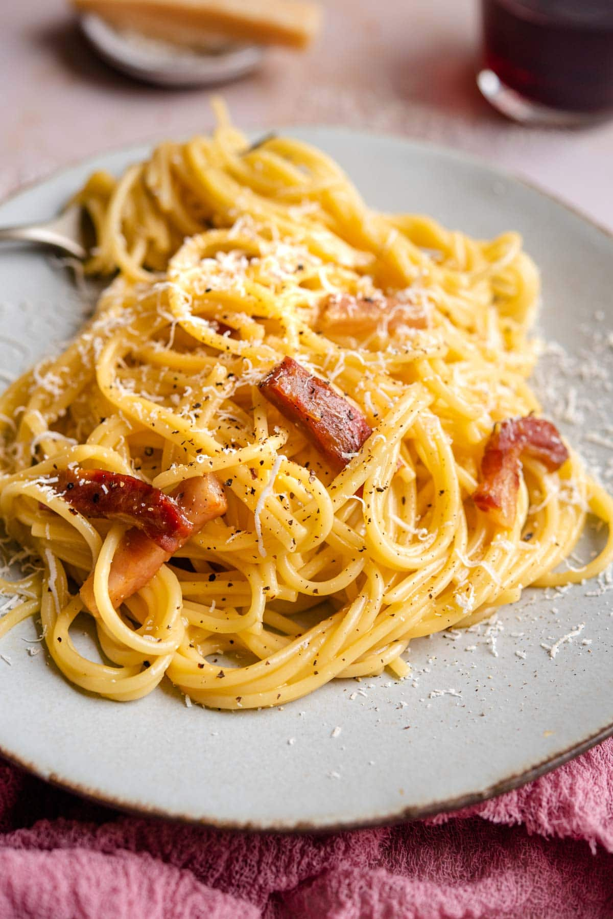 A side shot of spaghetti carbonara on a plate with a fork
