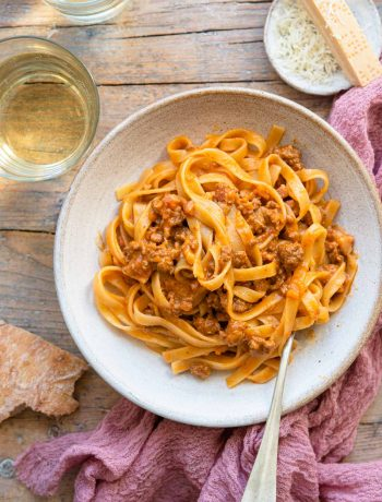 AN overhead shot of tagliatelle bolognese in a rustic bowl