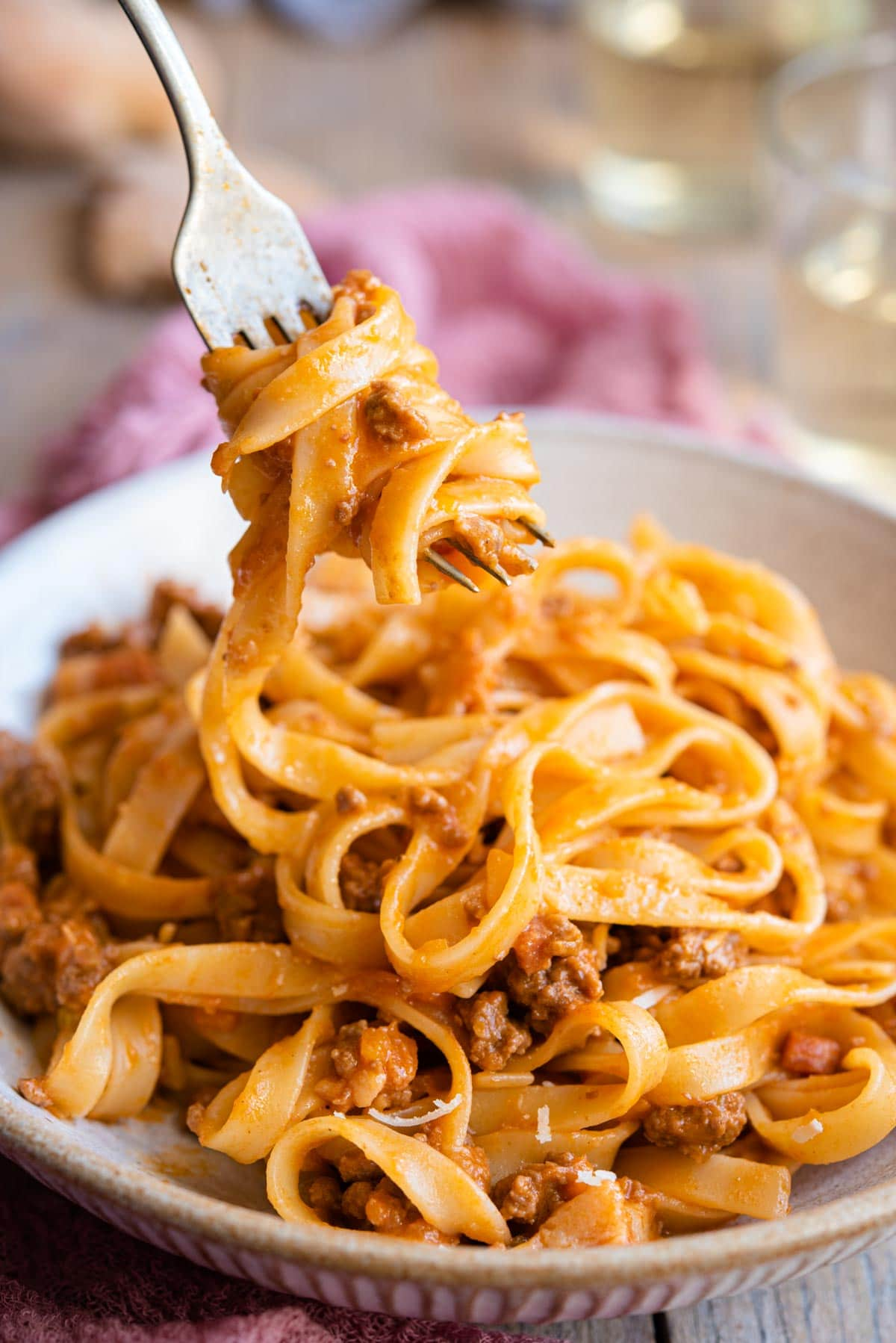 A close up of tagliatelli and bolognese sauce on a fork