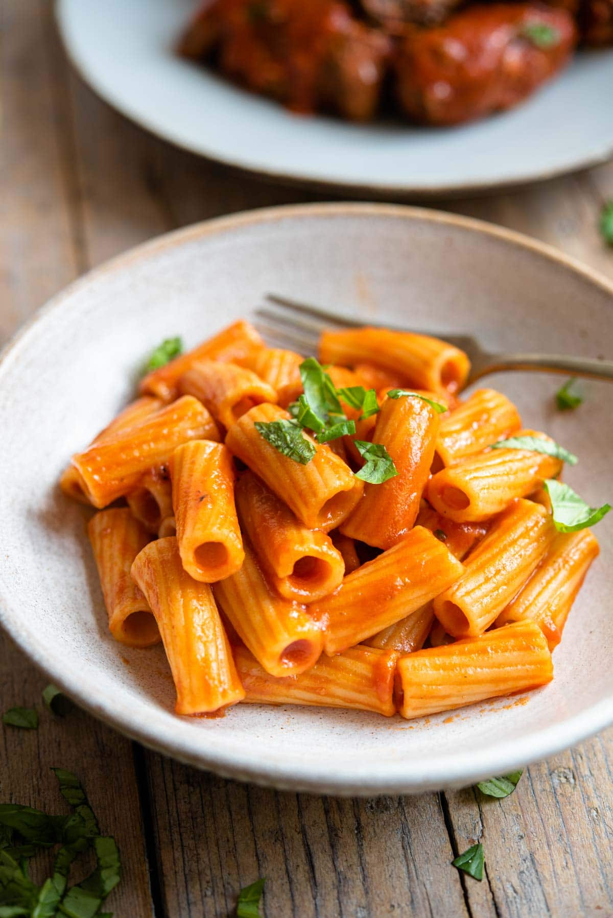 A side shot of pasta with tomato sauce in a bowl