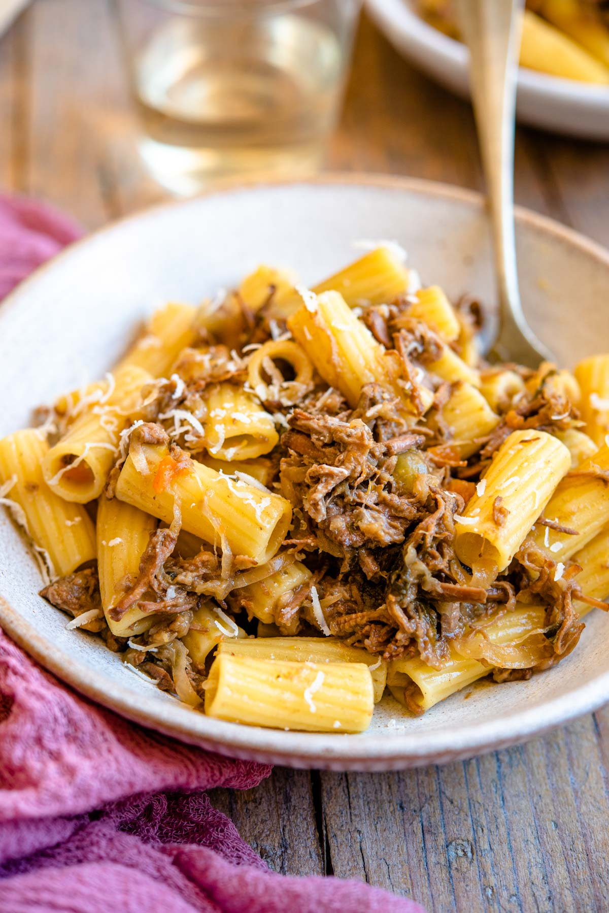 A side shot of a Neapolitan ragu tossed with rigatoni pasta in a rustic bowl