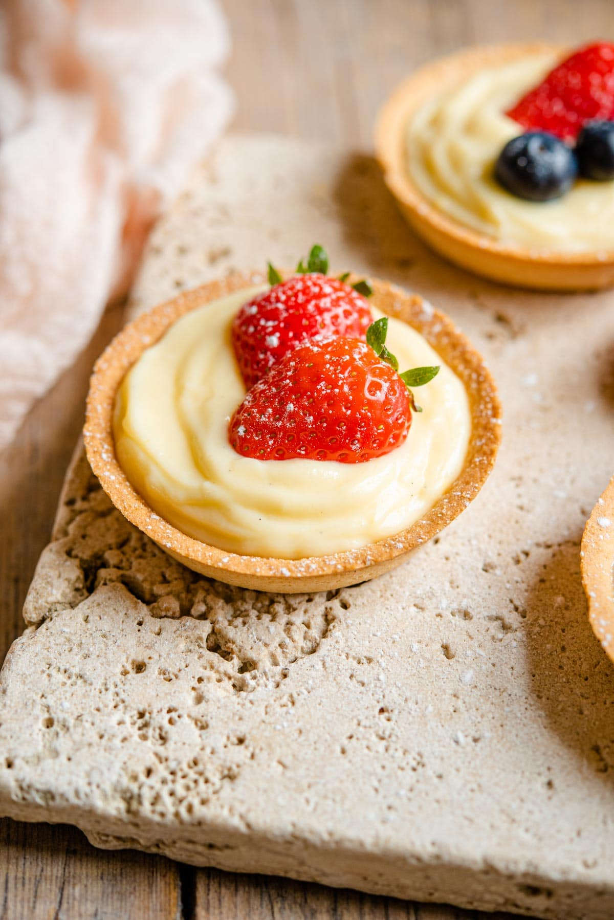 A small individual sized pie crust filled with Italian pastry cream and topped with two slices of strawberry.