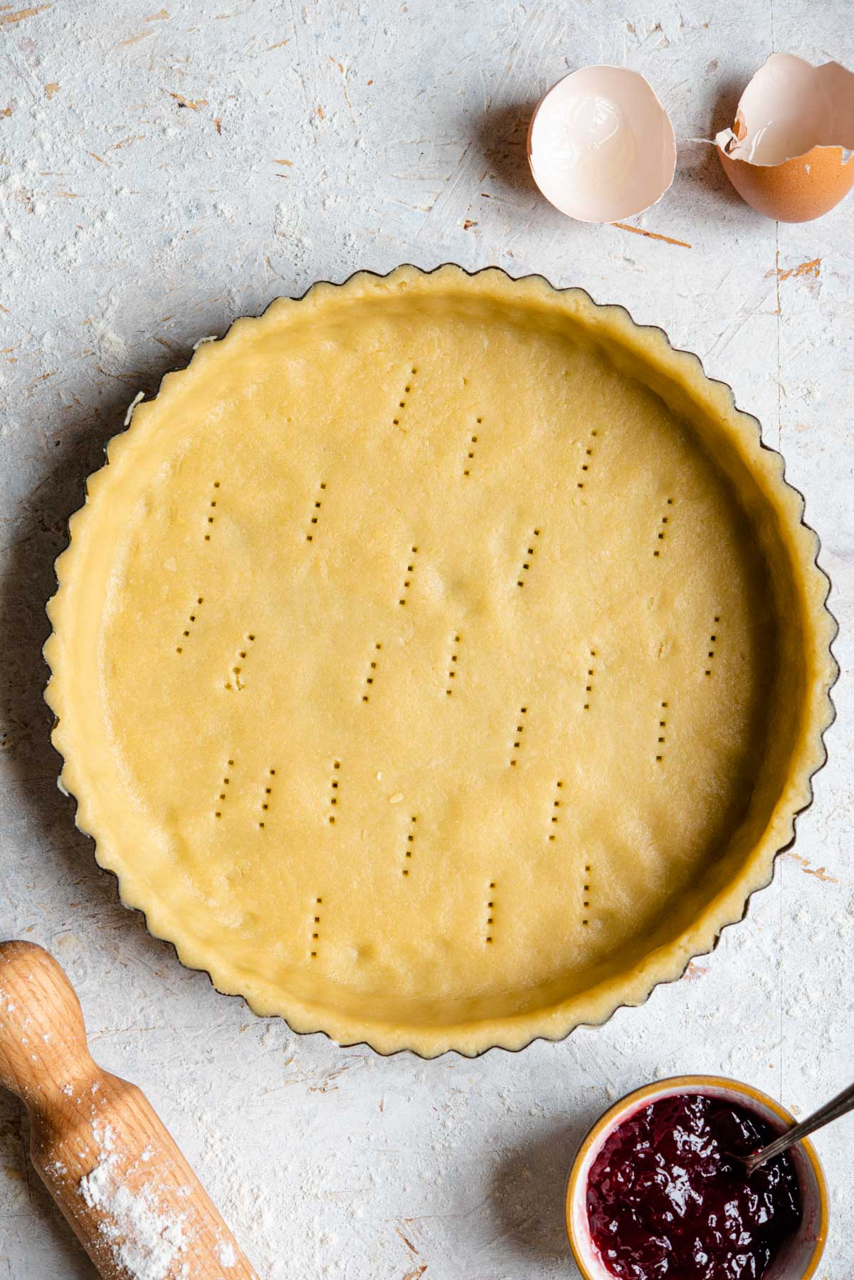 An overhead shot of raw sweet shortcrust pastry in a pie case
