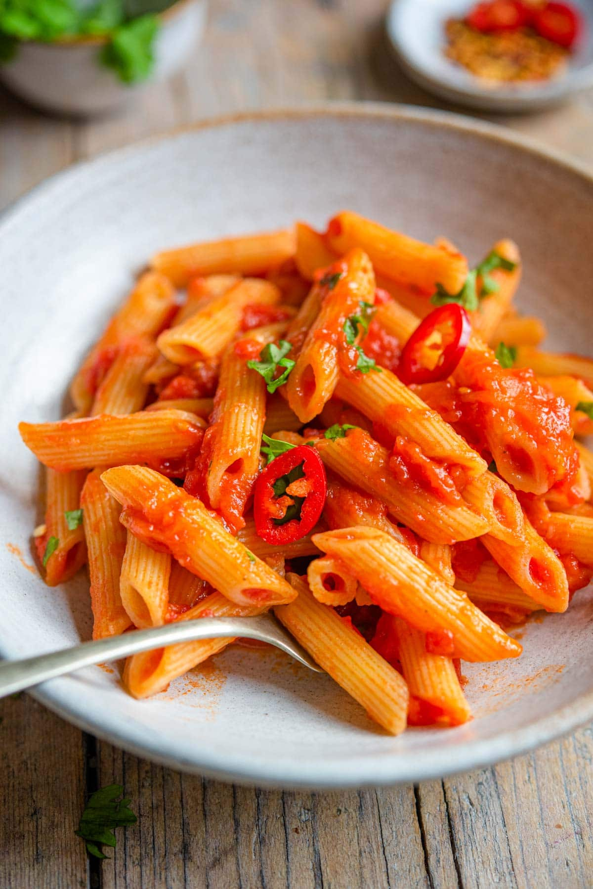 A close up of penne arrabbiata in a rustic bowl with a fork