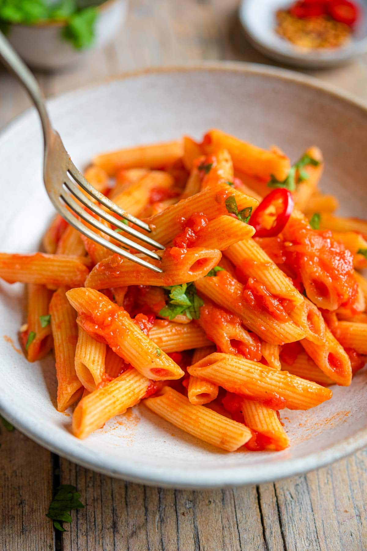 A close up of a fork picking up penne pasta from a bowl