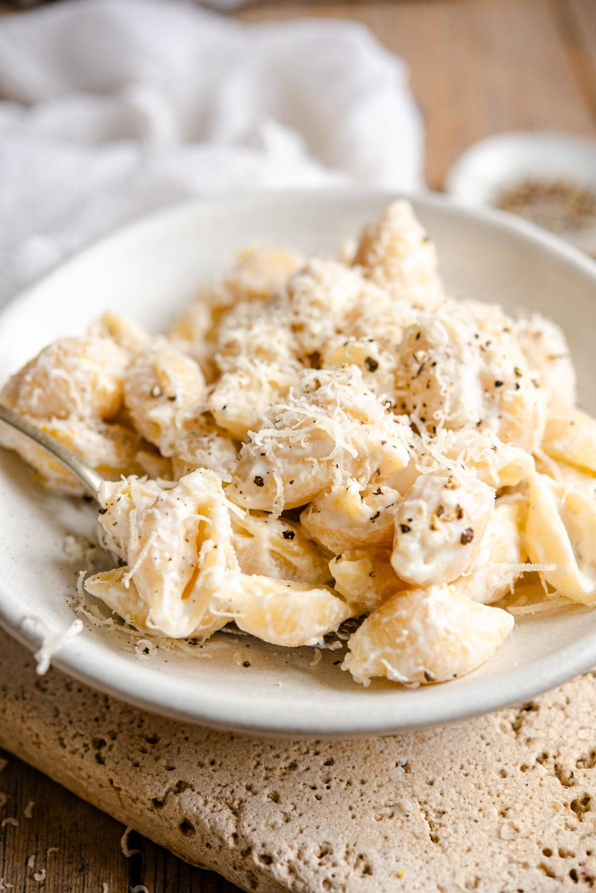A side shot of pasta shells with a ricotta sauce in a ceramic bowl