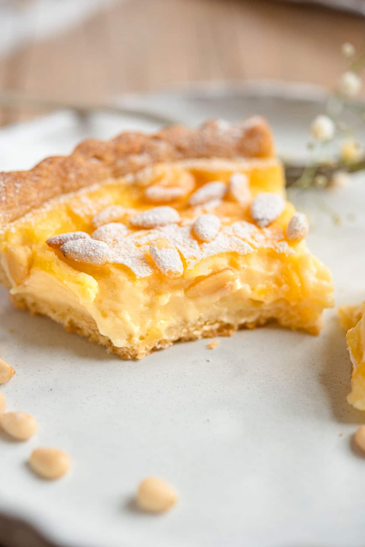 A close up of a slice of torta della nonna with a bite out
