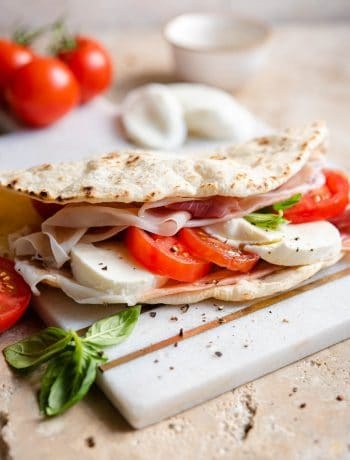 A Piadina flatbread stiffed with tomato, mozzarella and prosciutto on a marble board