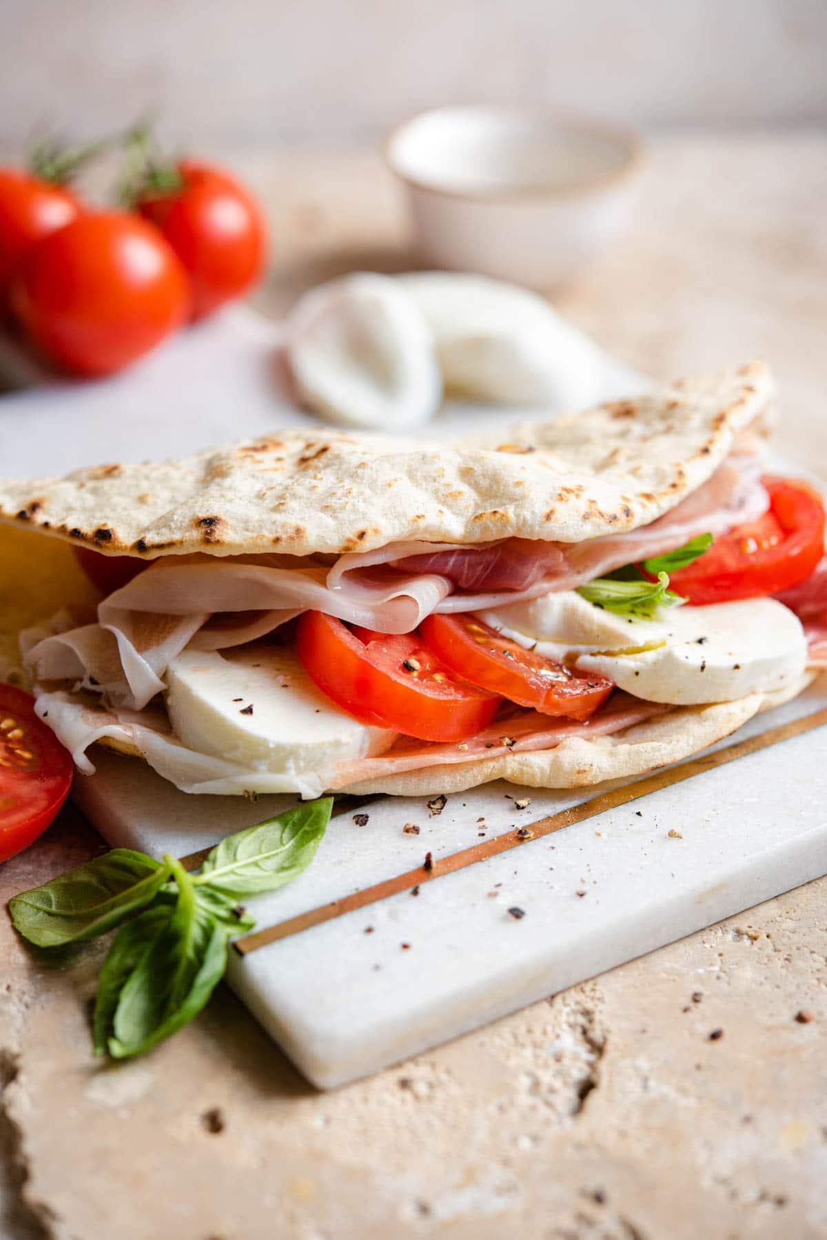 A Piadina flatbread stuffed with tomatoes, mozzarella and prosciutto sitting on a marble board