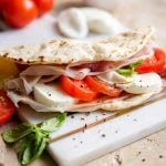 A close up of a piadina flatbread stuffed with tomatoes and mozzarella