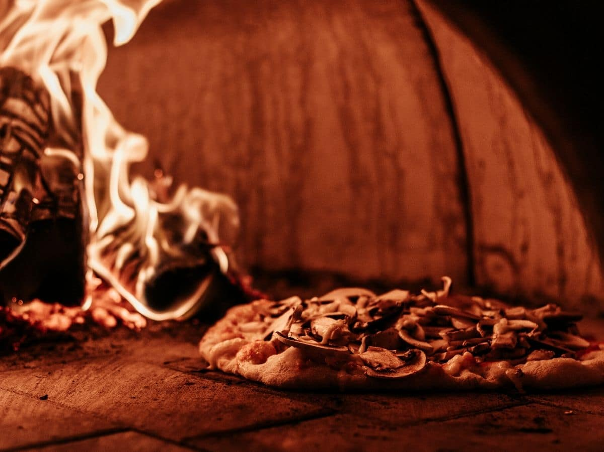 A photo of a pizza inside a wood fired pizza oven