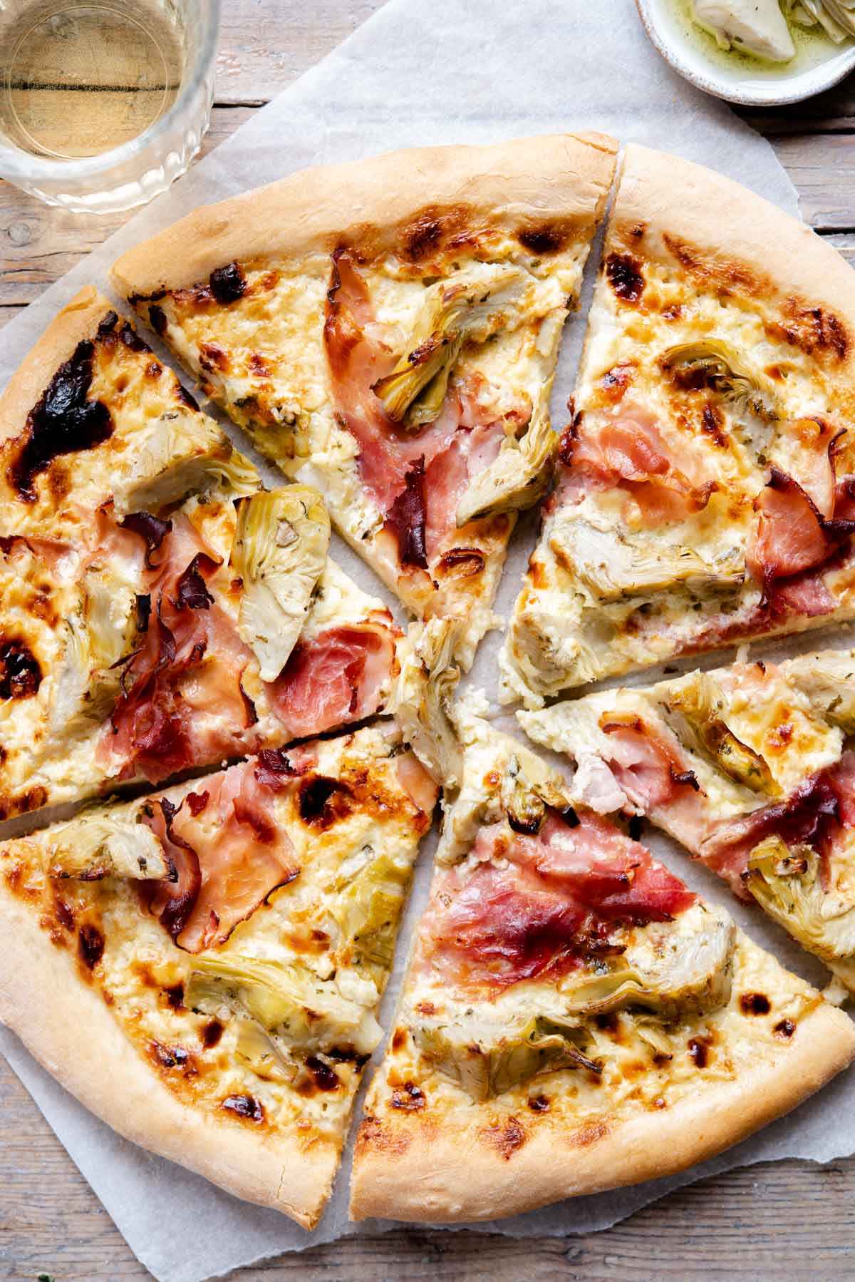 An overhead shot of an artichoke pizza cut into slices