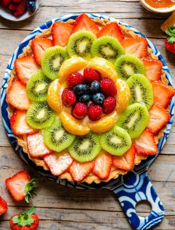 An overhead shot of a fruit tart layered with fresh fruit
