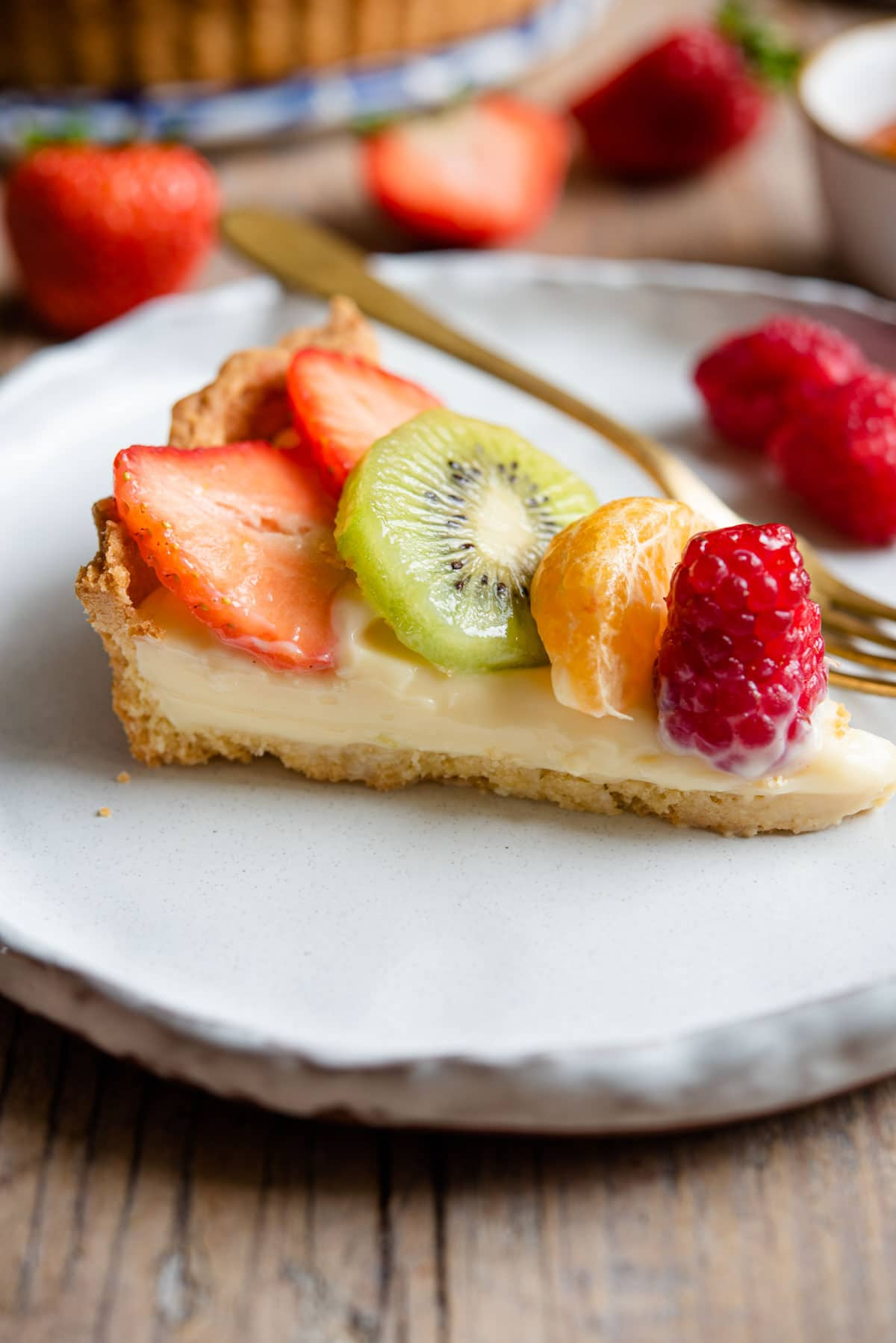 A slice of tart filled with pastry cream and fresh fruit