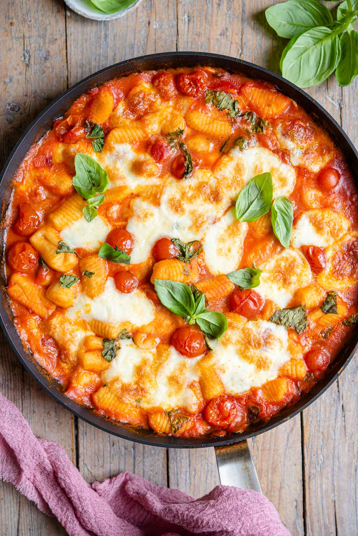 An overhead shot of gnocchi alla sorrentina in a skillet sitting on a wooden surface