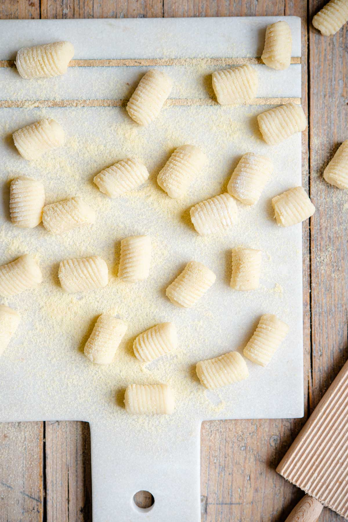 An overhead shot of potato gnocchi on a marble cutting board