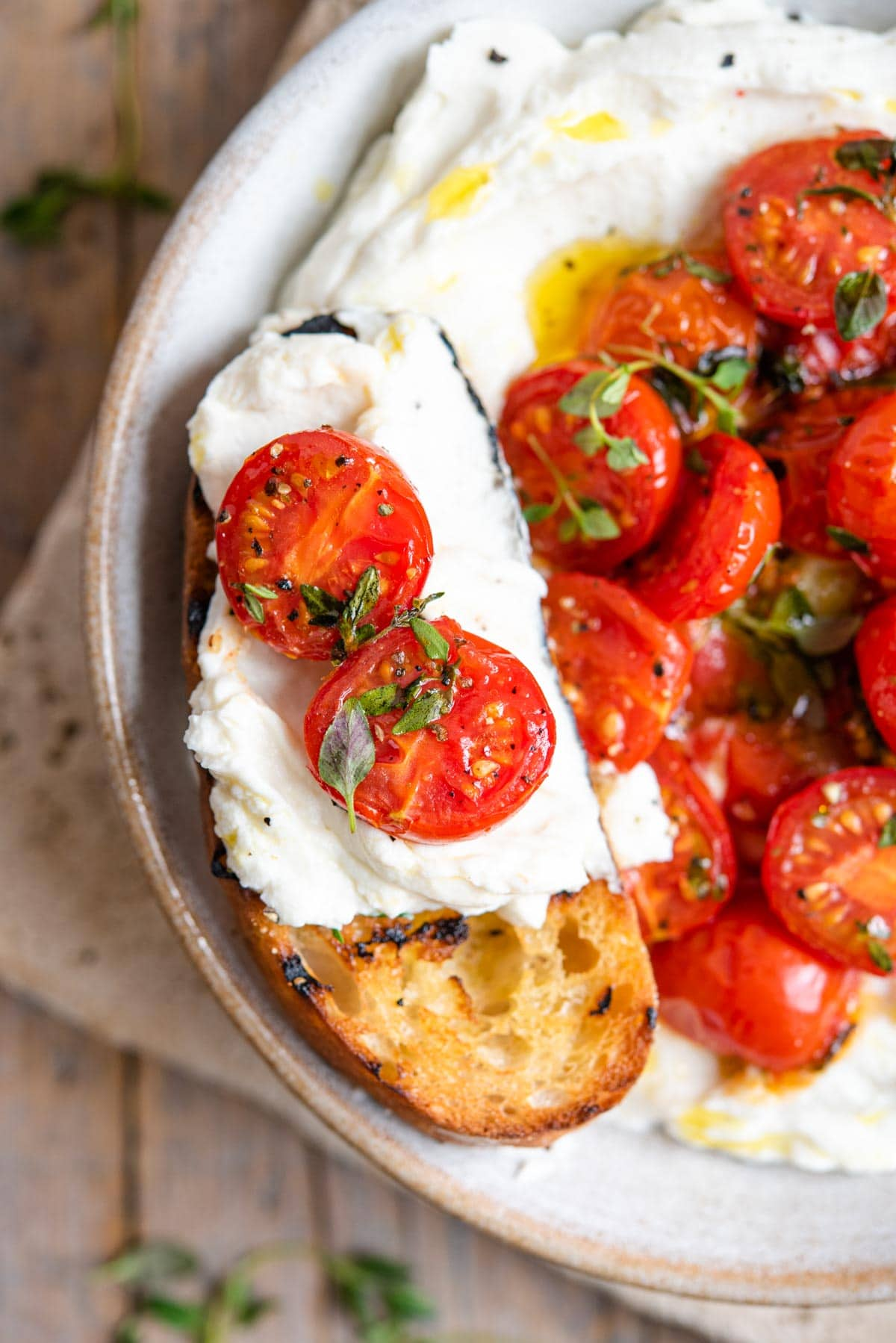 A close up of a slice of ciabatta bread topped with whipped ricotta and tomatoes