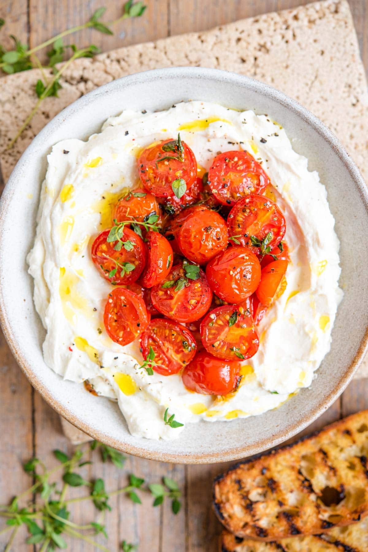 An overhead shot of ricotta in a serving bowl topped with roasted tomatoes