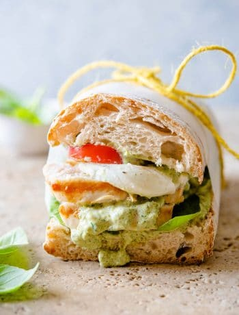 A close up of a ciabatta sandwich with chicken and pesto
