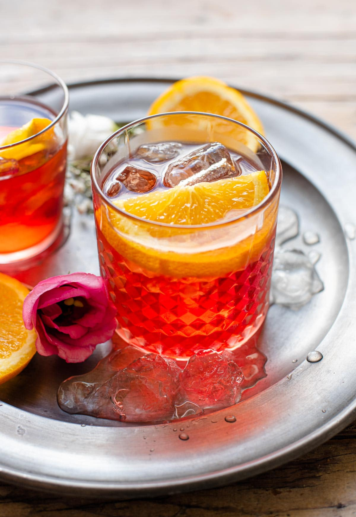 A Negroni cocktail in a glass with a slice of orange