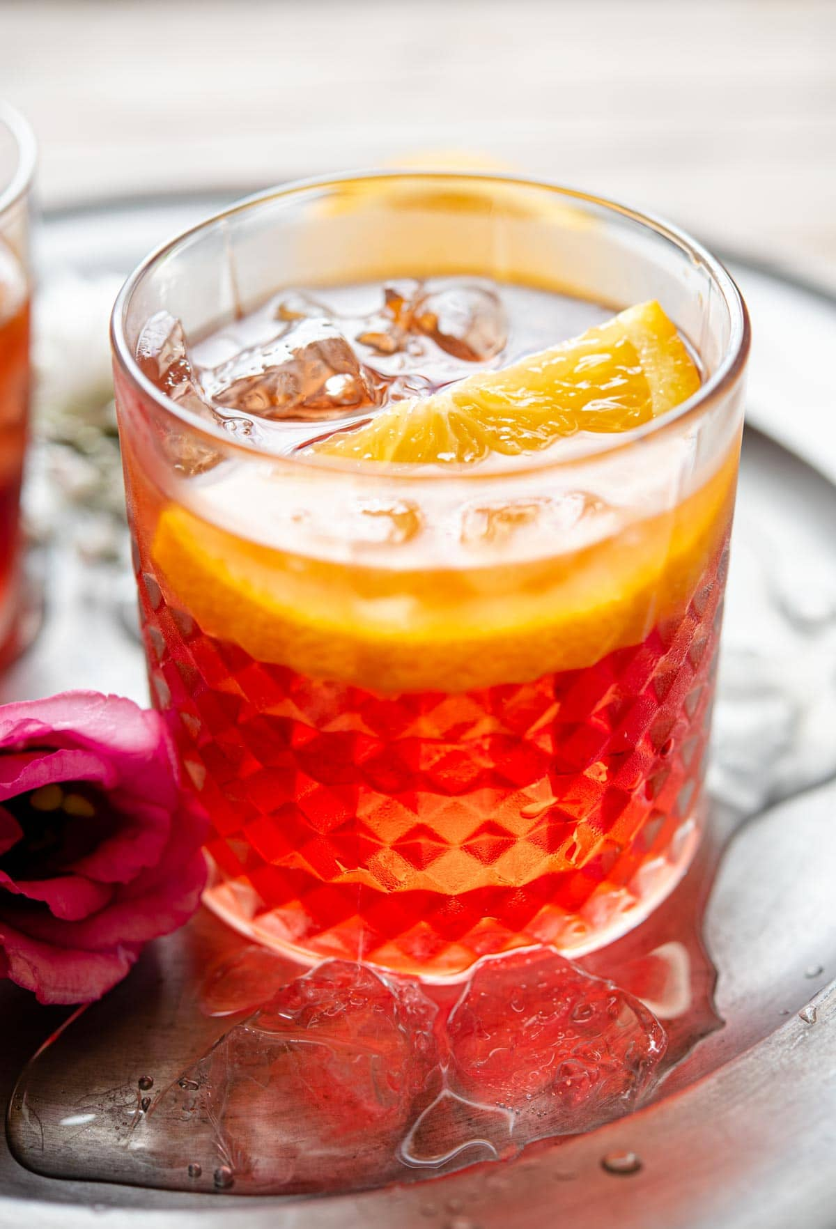 A close up of a negroni cocktail in a glass