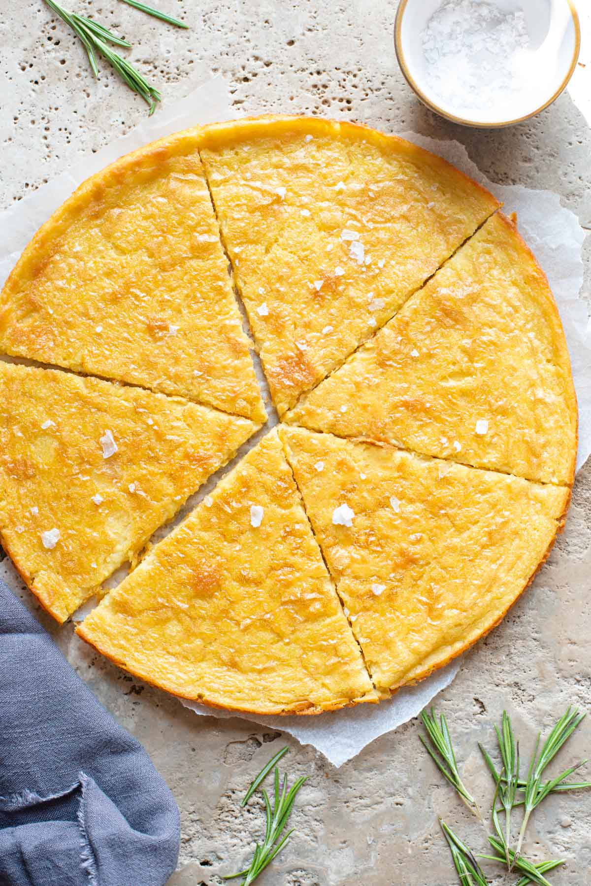 An overhead shot of a Tuscan chickpea flatbread on a stone worktop