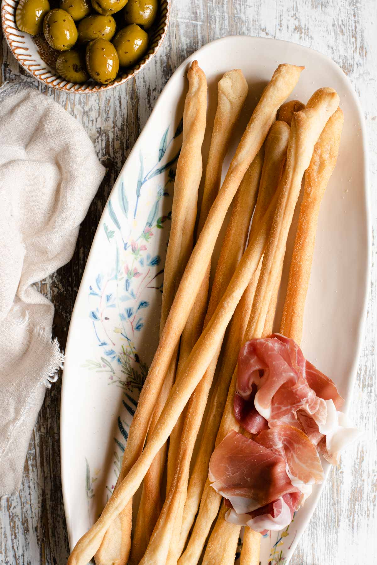 An overhead shot of Italian breadsticks on a serving plate with olives and prosciutto