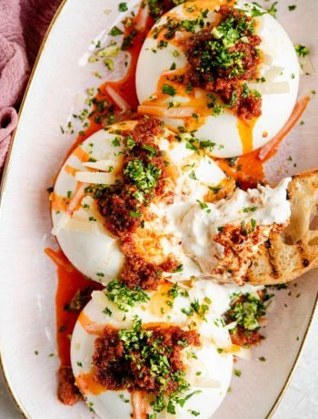 An overhead shot of burrata cheese on a serving plate with nduja and gremolata