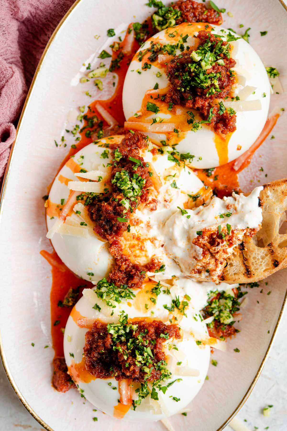 An overhead shot of burrata on a serving plate with 'Nduja and gremolata