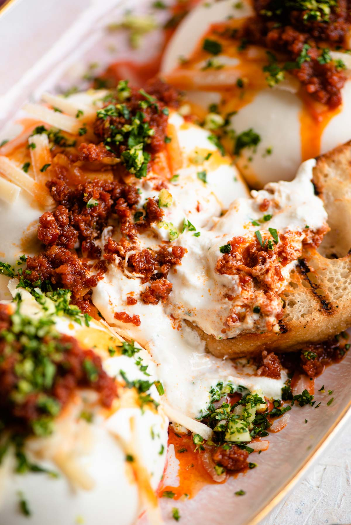 A close up of burrata cheese with 'Nduja and ciabatta bread