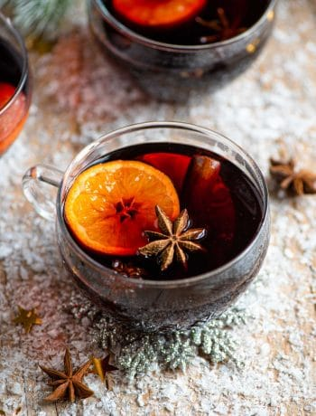 A mug of muled wine on a snowy wooden surface
