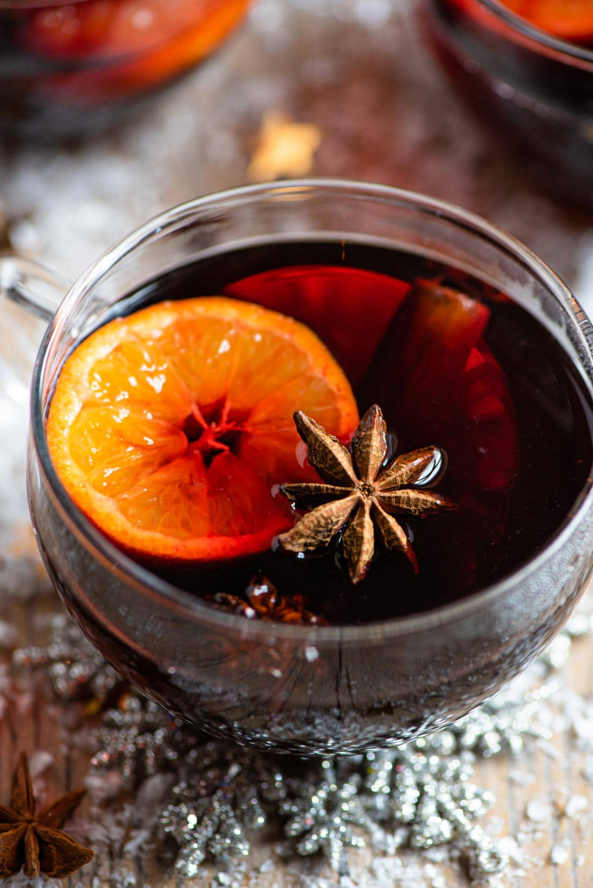 A close up of a mug of mulled wine with oranges, star anise and cinnamon